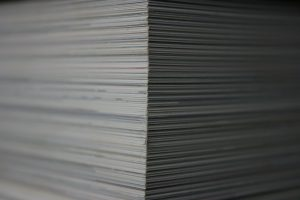 Photo showing the stacks of mortgage paperwork that a licensed real estate agent will help you sort through