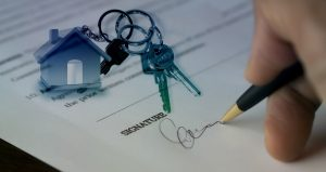 Photo showing a signature on a contract and keys in the background. Hiring a real estate agent is a smart choice for anyone buying a home.